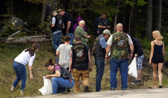 People recover personal items from the scene of a fatal accident on Route 2 in